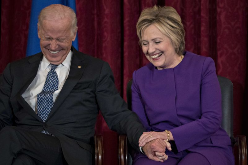 """Hillary Clinton, former secretary of state, right, and U.S. Vice President Joseph """"Joe"""" Biden laugh during an unveiling ceremony of Senate Democratic Leader Harry Reid's official portrait on Capitol Hill in Washington, D.C., U.S., on Thursday, Dec. 8, 2016. Reid, the tart-tongued ex-boxer known for pugilistic rhetoric about Republicans, is marking the end of his 34-year career in Congress with the unveiling of his official portrait that was painted by former Senate staffer Gavin Glakas. Photographer: Andrew Harrer/Bloomberg via Getty Images"""