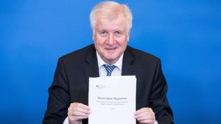 """BERLIN, GERMANY - JULY 10: German Interior Minister Horst Seehofer holds a copy of his """"master plan"""" concerning migration policy on July 10, 2018 in Berlin, Germany. The plan includes measures to stop migrants at the German border who have already registered in a different member country of the European Union and to return them there. The plan, which Seehofer kept secret for weeks, became a major point of dispute within the German government, pitting Seehofer against German Chancellor Angela Merkel. (Photo by Omer Messinger/Getty Images)"""