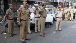 New Delhi, India - June 30, 2012: Indian policemen stand guard in the Spice Market area of Old Delhi. Police and military arrive in force during a high level visits of a U.S. Diplomat. Often time disrupting commerce and local business.