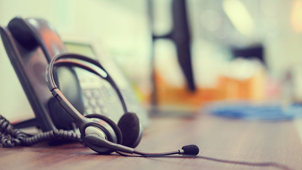 close up focus on call center headset device  headset VOIP system with telephone answer machine technology at operation office desk for hotline telemarketing and network operator concept