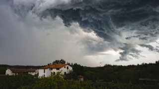 Dark day for agriculture, with hailstone stormy clouds above house between woods.