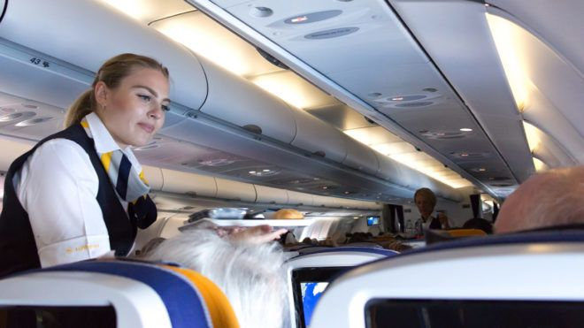 Munich: A female flight attendant is serving the lunch to a passenger sitting in the economy class of the route Munich - Vancouver of Lufthansa Airlines.