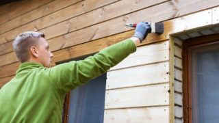painter with paintbrush painting house wood facade