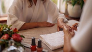 Manicurist hand shaping nails of young woman in salon. Woman in a nail salon receiving a manicure by a beautician