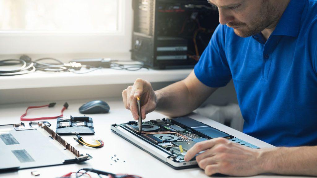 computer repair service - technician repairing broken laptop in office