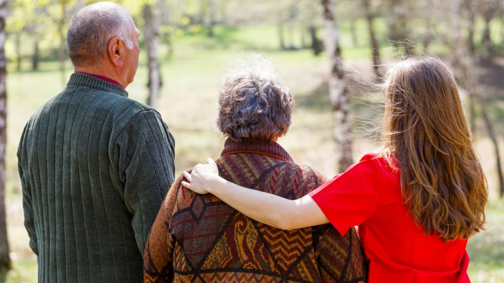 Photo of elderly couple and young caregiver walking in the nature