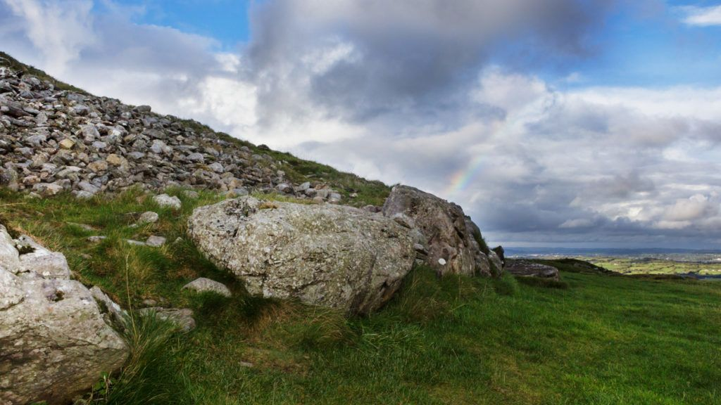 A large passage tomb, ritual chamber and landmark in loughcrew, county meath, Ireland. A rainbow arcs in the distance over rolling Irish hills.