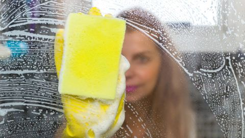 Great concept of domestic cleaning, young blond woman cleaning glass from the bathroom.