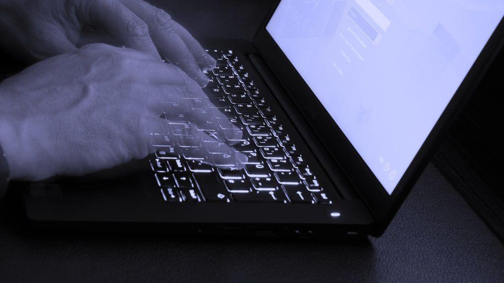 Das Bild zeigt wie sich jemand an einem Hotel Schreibtisch am Laptop einloggt. Symbolik für: mobiles Büro, Erreichbarkeit, Internet, Information, Darknet