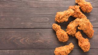 Fried chicken drumstick on the wooden background.