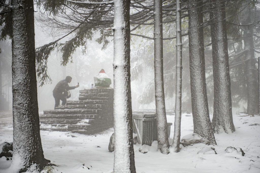 Kékestetõ, 2019. május 6. Fényképet készít egy férfi a Kékes csúcsát jelölõ kõrõl a hóesésben 2019. május 6-án. MTI/Komka Péter