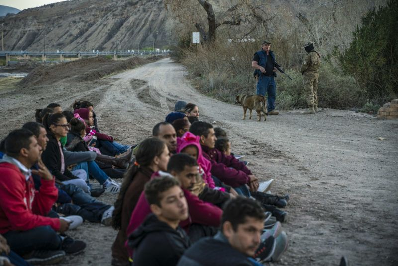 """Propery owner Jeff Allen, 56, (rear left) stands near a group of about 30 Brazilian migrants, who had just crossed the border at his property in Sunland Park, New Mexico on the US-Mexico border on March 20, 2019, as they wait for US Border Patrol to pick them up. - The militia members say they will patrol the US-Mexico border near Mt. Christo Rey, """"Until the wall is built."""" (Photo by Paul Ratje / AFP)"""