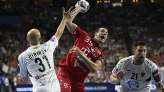 Vardar's Timur Dibirov and Veszprem's Kentin Mahe (C) vie during the EHF Champions League final handball match between HC Vardar and Telekom Veszprem in Cologne, western Germany, on June 2, 2019. (Photo by INA FASSBENDER / AFP)