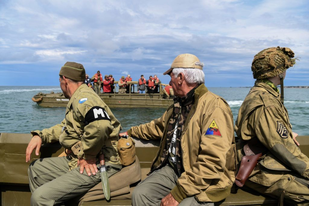 Men dressed as GIs sit on a DUKW (colloquially known as Duck), a six-wheel-drive amphibious modification of the 2 1/2-ton CCKW trucks used by the US military during World War II, on June 4, 2019 off the shores of Arromanches-les-Bains, as part of events for the 75th anniversary of D-Day landings. (Photo by ALAIN JOCARD / AFP)