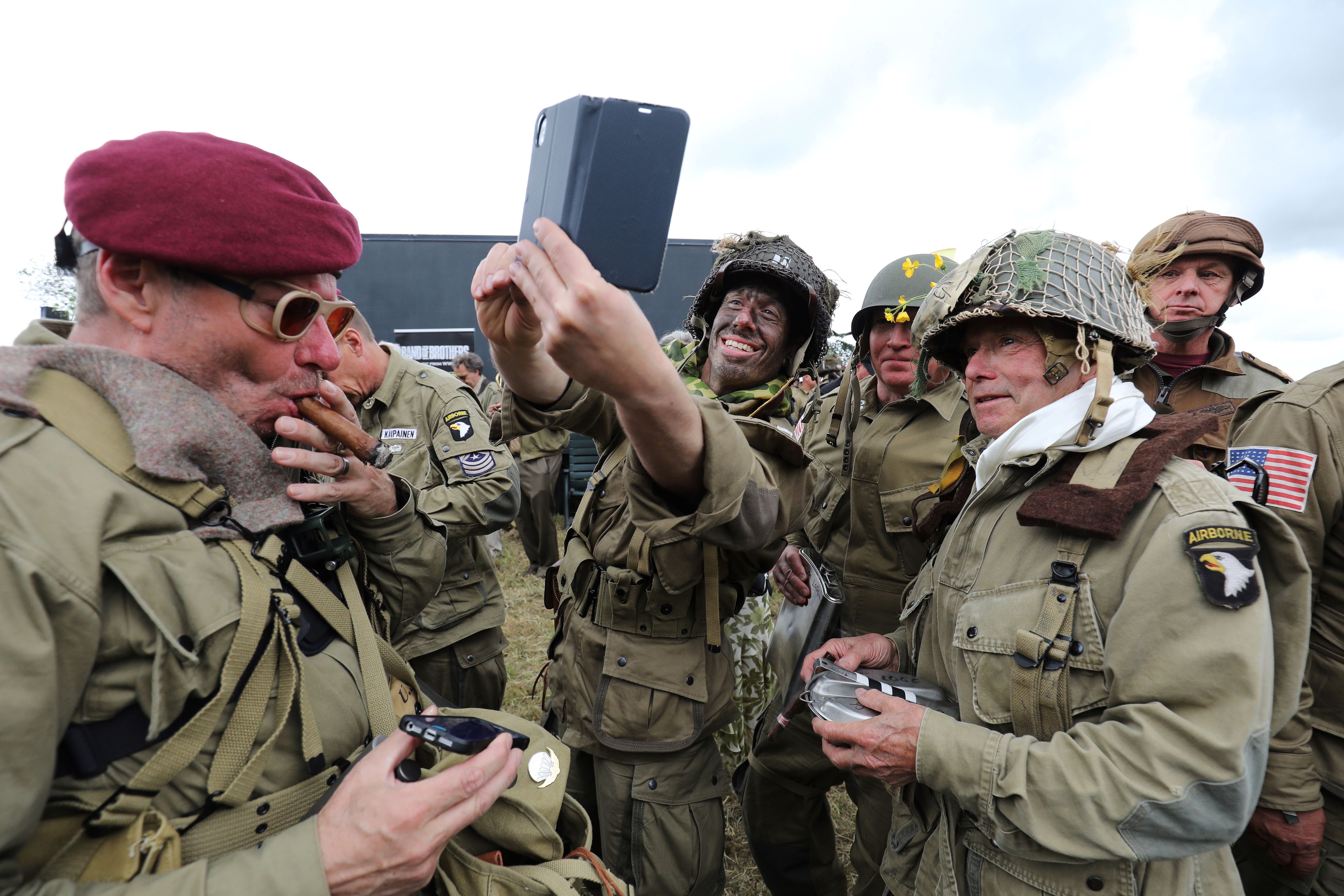 WWII enthusiasts dressed in period US and British paratrooper uniforms takes selfies during a parachute drop over Carentan, Normandy, north-western France, on June 5, 2019, as part of D-Day commemorations marking the 75th anniversary of the World War II Allied landings in Normandy. (Photo by Ludovic MARIN / AFP)