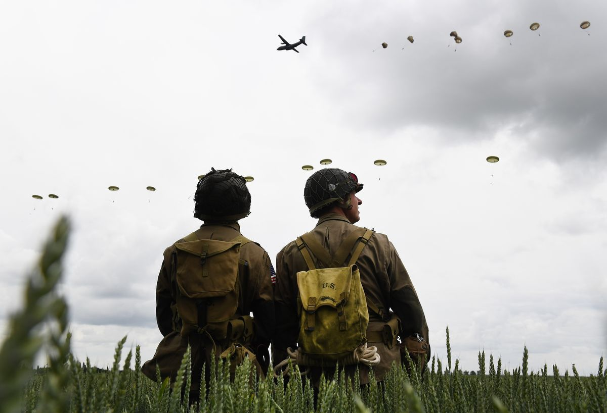 Men dressed as US GIs look at paratroopers from Britain's 16 Air Assault Brigade and France's 11th Parachute Brigade performing a jump over Sannerville, north-western France, on June 5, 2019, prior to D-Day commemorations marking the 75th anniversary of the World War II Allied landings in Normandy. (Photo by Fred TANNEAU / AFP)