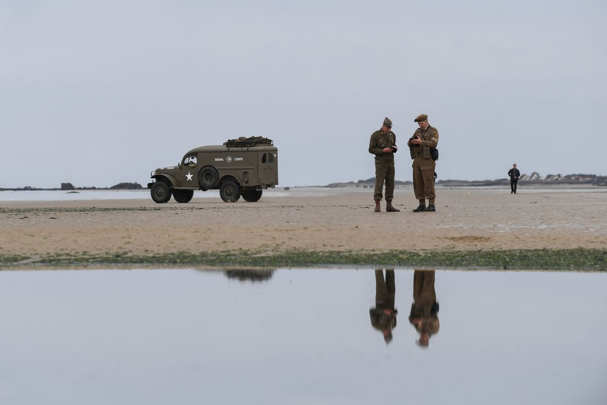 Men wearing British army uniforms stand next to a US army Signal Corps vehicle used during World War II, on the beach in Arromanches-les-Bains, on June 5, 2019, prior to D-Day commemorations marking the 75th anniversary of the World War II Allied landings in Normandy. (Photo by ALAIN JOCARD / AFP)
