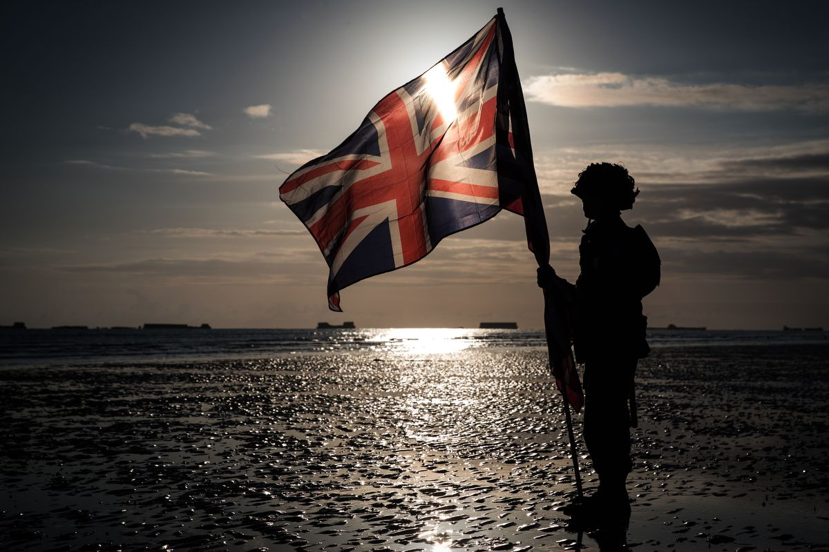 This picture taken on June 6, 2019 shows the silhouette of a soldier holding an English flag on the beach of Arromanches, during the D-Day commemorations marking the 75th anniversary of the World War II Allied landings in Normandy. (Photo by JOEL SAGET / AFP)