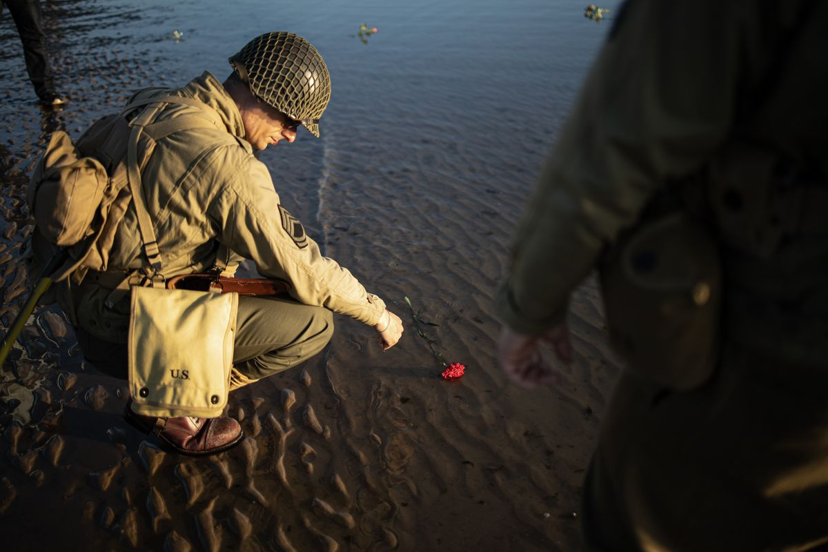 A WWII enthousiast tosses a flower in the sea on Omaha beach, near Colleville-sur-Mer, Normandy, northwestern France, in the early morning of June 6, 2019 during the D-Day commemorations marking the 75th anniversary of the World War II Allied landings in Normandy. (Photo by FEDERICO SCOPPA / AFP)