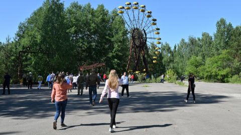 Visitors walk in the ghost city of Pripyat during a tour in the Chernobyl exclusion zone on June 1, 2019. - HBOís hugely popular television series ìChernobylî has renewed interest around the world on Ukraineís 1986 nuclear disaster with authorities reporting a 30% increase of tourist demands to visit the affected area and tourist operators forecasting that number of tourists visiting the site may double this year up to 150.000 persons. (Photo by Genya SAVILOV / AFP)