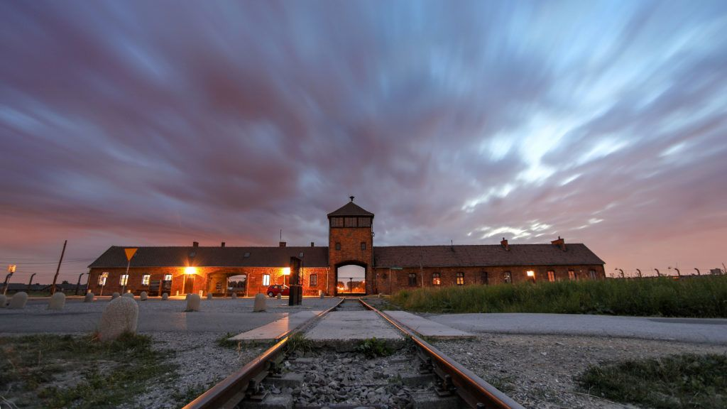 The gate of the former concentration camp Auschwitz-Birkenau can be seen in the evening in Oswiecim, Poland, 26 June 2017 (time exposure). The major paramilitary organization in Nazi Germany, SS (Schutzstaffel, lit. 'Protection Squadron'), ran the concentration and death camp between 1940 and 1945. Incoming deportees were selected into different groups on the ramp between the tracks right after they arrived in Birkenau. The people who were not able to work (elderly, weak, women, children) were sometimes sent to the gas chambers directly without registration. Approximately 1.1 to 1.5 million people, most of them Jewish, have been killed in the camp and its satellites. Auschwitz stands as the symbol for the industrialized mass murder and the holocaust of Nazi Germany.  Photo: Jan Woitas/dpa-Zentralbild/dpa | usage worldwide