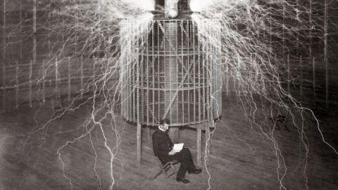 "Nikola Tesla sitting in his Colorado Springs laboratory with his ""Magnifying transmitter"" - 1899 (Multiple exposure) -  portrait de Nikola (Nikolaj) Tesla (1857-1943) dans son laboratoiore. ©Leemage"