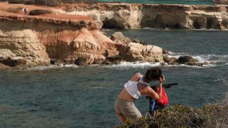 A tourist takes photos of the Sea Caves in Cyprus' near the town of Pegeia in western Cyprus, on May 9, 2018, as construction workers build six new luxury villas. - In a string of caves along the coast of Cyprus, a colony of monk seals -- the most endangered mammals in the Mediterranean, numbering only around 300 -- has found refuge. But now environmentalists and residents are accusing developers of endangering their habitat by building luxury villas on top of the caves. (Photo by Emily IRVING-SWIFT / AFP)