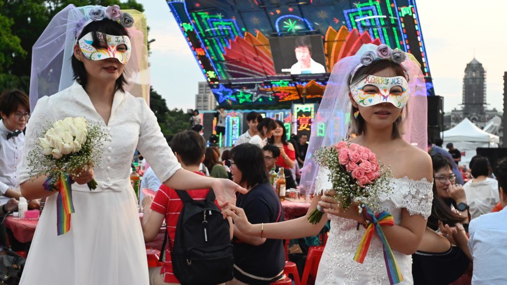A gay couple pose for photographs during a mass wedding banquet in front of the Presidential Palace in Taipei on May 25, 2019. - Taiwan made history on May 24 with Asia's first legal gay weddings as same-sex couples tied the knot in jubilant and emotional scenes, the culmination of a three-decade fight for equality. (Photo by Sam YEH / AFP)