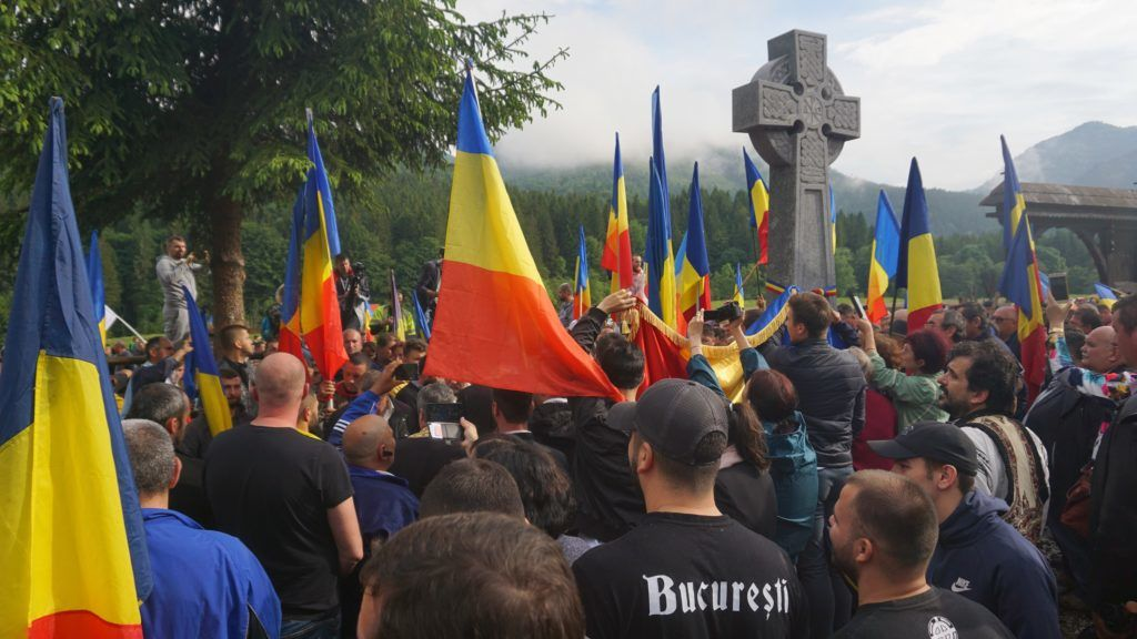 Romanian nationalists listen to the religious service of a christian orthodox priest as they forced the entrance of military cemetery in the village of Valea Uzului, Romania June 6, 2019. - The cemetery is at a center of a dispute between Romanians and the Hungarians as it shelter, according to romanian historians, the remains of Hungarian, Romanian, Russian, Serbian and Austrian soldiers fallen during WWI and WWII. (Photo by EGYED UFO ZOLTAN / AFP)