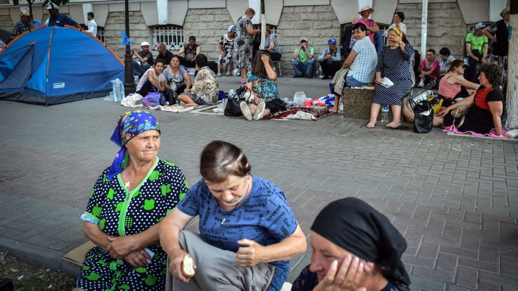 Supporters of the Democrat Party of Moldova (PDM), ruled by Vladimir Plahotniuc, sit on the pavement after camping in the front of The Ministry of Interior headquarters in Chisinau city on June 10, 2019. - Moldova's acting president Pavel Filip on June 9, 2019 dissolved parliament and called snap elections, as a political crisis rocks the ex-Soviet country. Filip signed a decree dissolving parliament and calling snap elections for September 6 after the Constitutional Court earlier on June 9, 2019 suspended pro-Russia president Igor Dodon and named Filip, who is the acting prime minister, as acting president. (Photo by Daniel MIHAILESCU / AFP)