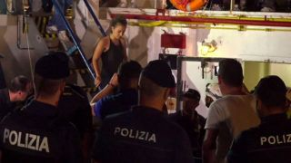 An image grab taken from a video released by Local Team on June 29, 2019, shows the Sea-Watch 3 charity ship's German captain Carola Rackete being arrested by Italian police, in the Italian port of Lampedusa, Sicily. - The Sea-Watch 3 charity ship carrying dozens of migrants rescued off Libya forced its way into the Italian port of Lampedusa on June 28 night after a lengthy standoff, the charity said. The boat's German captain Carola Rackete, 31, was arrested and the 40 migrants were still on board after the vessel docked. After manoeuvring the ship into port without permission, Rackete was arrested by police for refusing to obey a military vessel, a crime punishable by between three and 10 years in jail. She offered no resistance and was escorted off the vessel without  handcuffs. (Photo by Anaelle LE BOUEDEC / various sources / AFP) / Italy OUT
