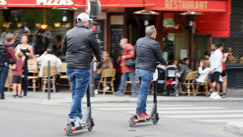 30 May 2020, France (France), Paris: Two men drive e-scooters on a street in the centre of Paris. Photo: Waltraud Grubitzsch/dpa-zentralbild/ZB
