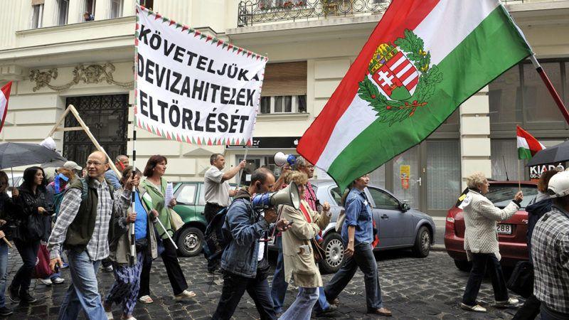 """Budapest, 2013. június 25.Tüntetők vonulnak egy """"Követeljük a devizahitelek eltörlését"""" feliratú transzparenssel a Kúria épületétől a Képviselői Irodaházhoz 2013. június 25-én. A tüntetők korábban a Kúria épülete előtt demonstráltak a devizahitel-károsultak védelmében, miközben a legfelsőbb bírói fórum egy devizahiteles ügyét tárgyalta.MTI Fotó: Kovács Attila"""