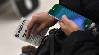 Budapest, 2018. február 6. Okostelefonját használja egy ügyfél sorszámával kezében az OTP Bank újonnan átadott bankfiókjában a fõvárosi Corvin Plaza bevásárlóközpontban 2018. február 6-án. MTI Fotó: Illyés Tibor