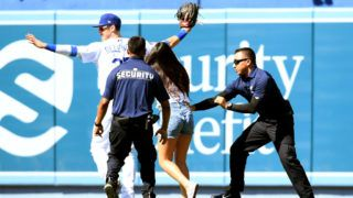 LOS ANGELES, CALIFORNIA - JUNE 23:  Cody Bellinger #35 of the Los Angeles Dodgers reacts as a fan chases after him on the field during the ninth inning against the Colorado Rockies at Dodger Stadium on June 23, 2019 in Los Angeles, California. (Photo by Harry How/Getty Images)