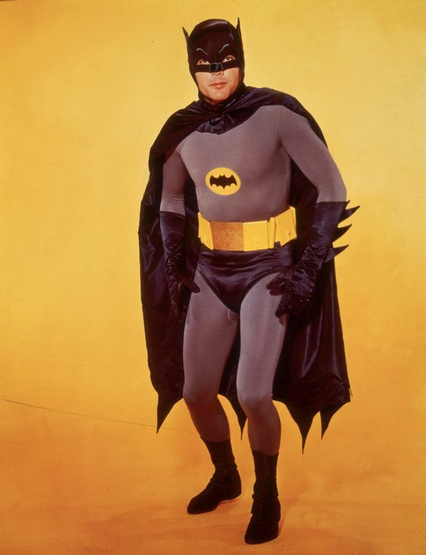 circa 1966:  American actor Adam West poses in costume as Batman in front of a yellow backdrop in a promotional portrait for the television series, 'Batman'.  (Photo by Hulton Archive/Getty Images)