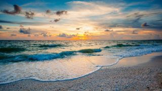 Marco Island in Florida has beautiful sunsets. The waters of the Gulf of Mexico roll in over seashells deposited on the beach.