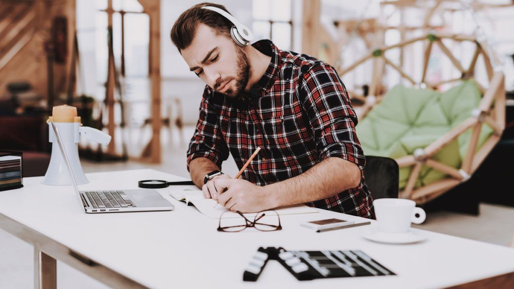 Creative Worker. Listen Music. Working. Ideas. Light Bulb. Glasses. Laptop. Comfortable. Project. Sit. Brainstorm. Young Guy. Businessman. Work. Office. Businesspeople. Workplace. Inspiration.