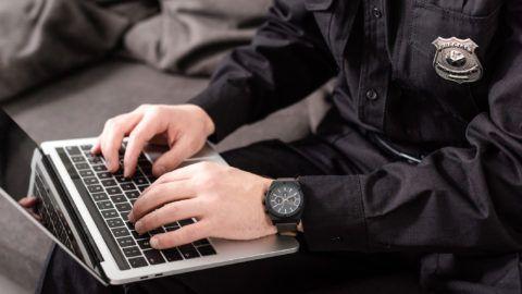 cropped view of policeman typing on laptop keyboard
