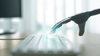 Robot with artificial intelligence is working on a computer. Robotic arm is pushing a keys on a computer keyboard.