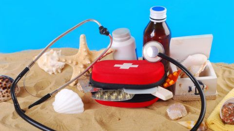 """""""first aid box with medicines,thermometer and stethoscope on the beach as healthy summer holiday concept"""""""