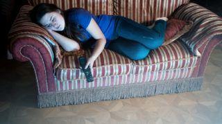 Beautiful woman sleeping on sofa while watching TV