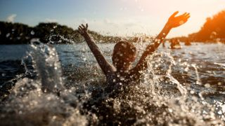child swim in lake or river and have fun with drops;