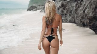 tattooed young girl in black swimsuit posing on the beach, tunn with her back to camera. Beautiful blonde woman with long hair relaxing at the ocean. Concept of sporty model, swimwear.