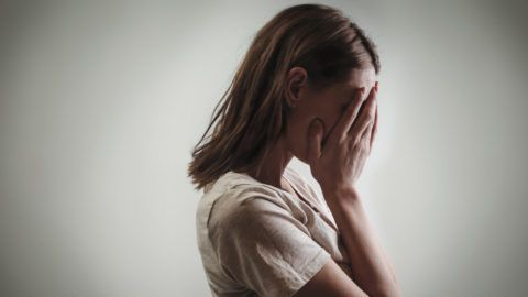 Portrait of depressed woman, covering face with her hands, side view