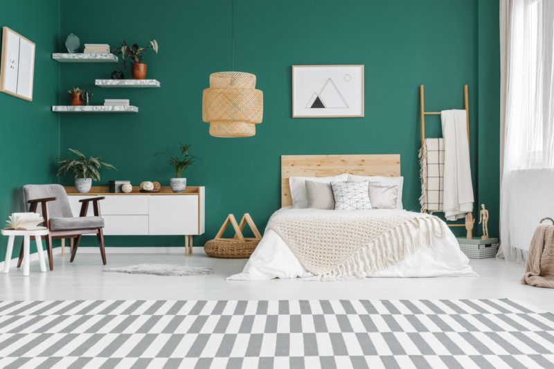 Geometric carpet in spacious green bedroom interior with grey armchair and poster above bed