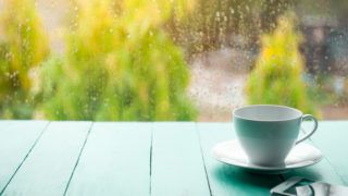 White coffee cup with mobile phone on old green wooden floor with raining background in the garden and natural scenery.