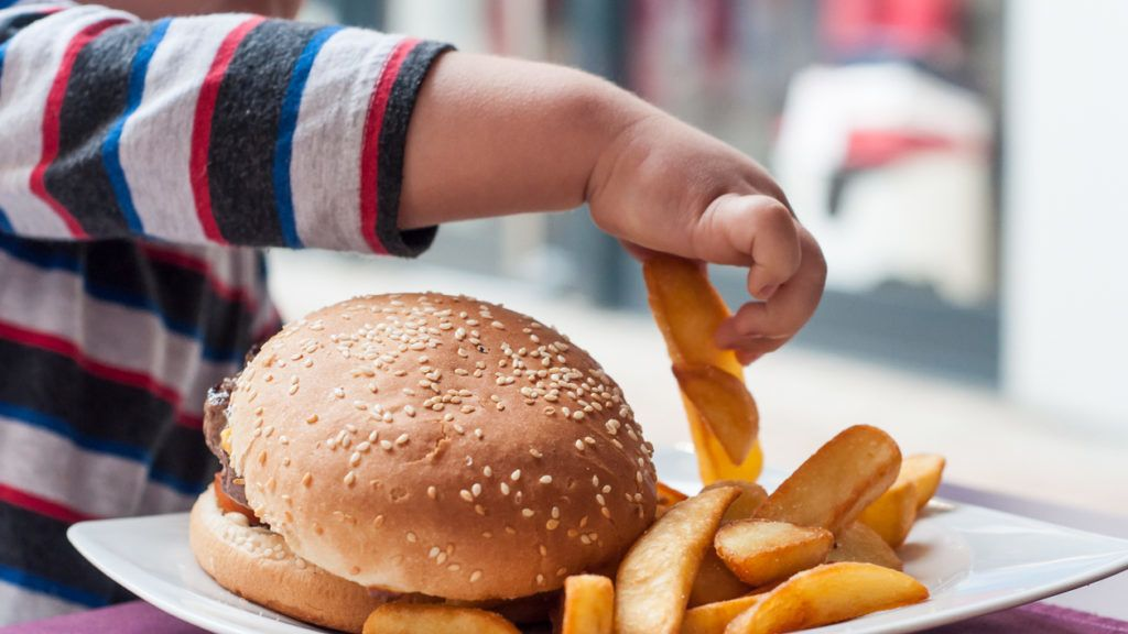 closeup of little boy hand eating hamburger and french fries at restaurant
