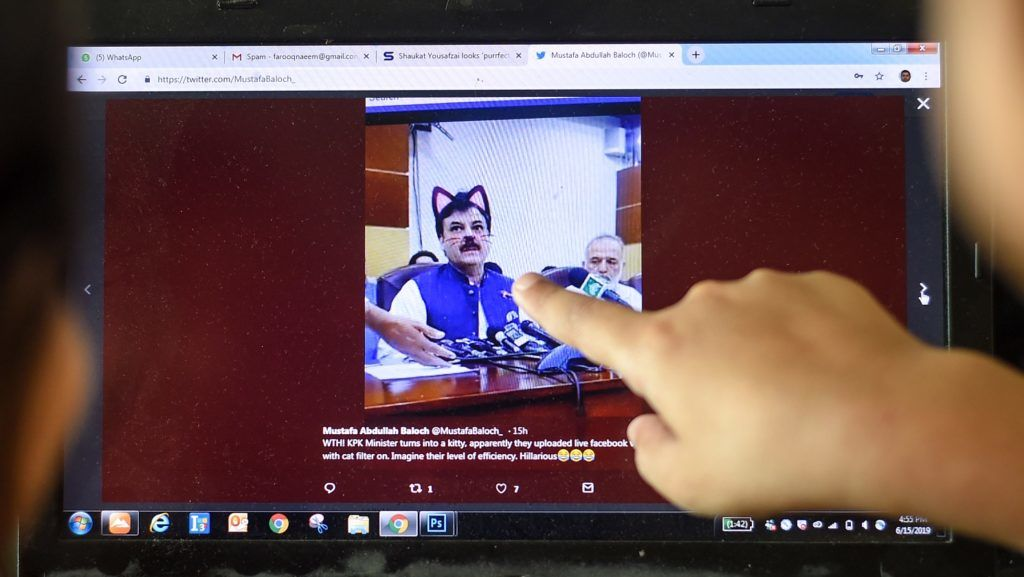 Pakistani children point at a computer screen showing a screen grab of a press conference attended by provincial minister Shaukat Yousafzai and streamed live on social media, in Islamabad on June 15, 2019. - A minister in Pakistan's northwestern Khyber Pakhtunkhwa province had to face hilarious situation after his entire media talks went live with a cat filter on by his social media team. (Photo by FAROOQ NAEEM / AFP)