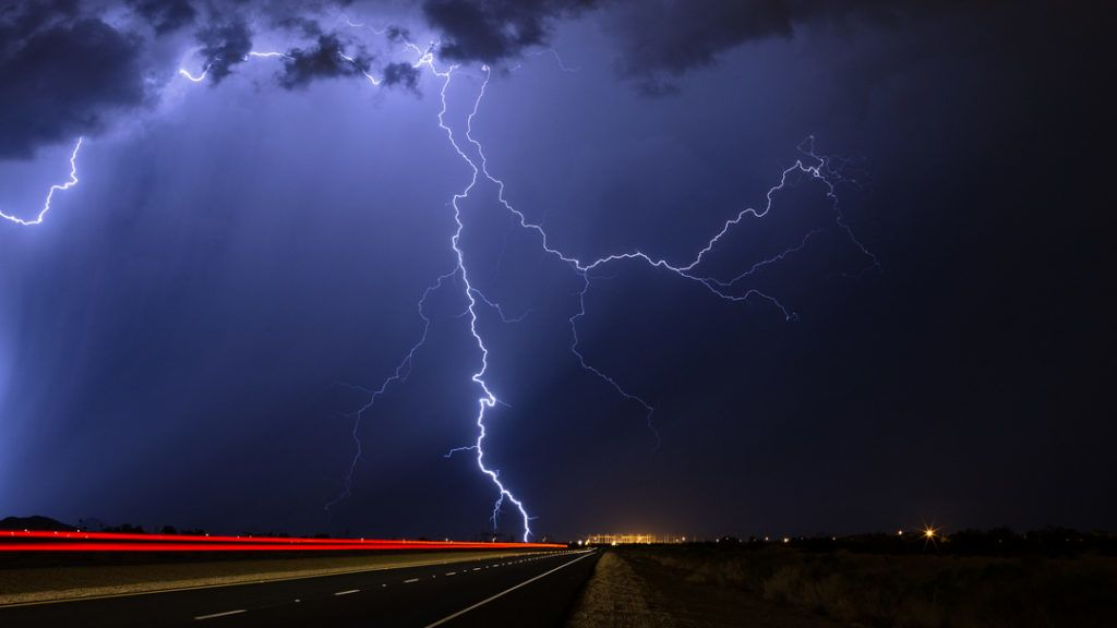 Lightning strikes during a nighttime thunderstorm as cars pass on a nearby highway.